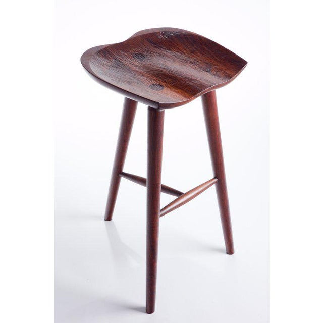A studio made, hand crafted stool in Walnut. Hand chiseled, saddled seat, with through mortise and tenon joinery as a...