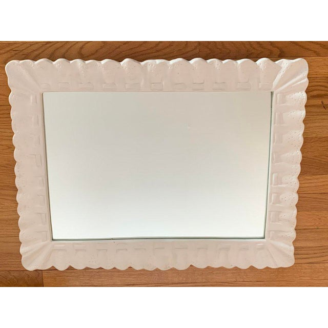 Heavy rectangular mirror cast in plaster in the form of gathered eyelet fabric, loosely stitched with a ribbon. The mirror...
