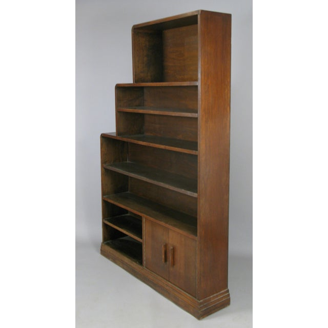 a very handsome pair of 1940s walnut bookcases in a skyscraper form, with adjustable shelves in two of the sections in...