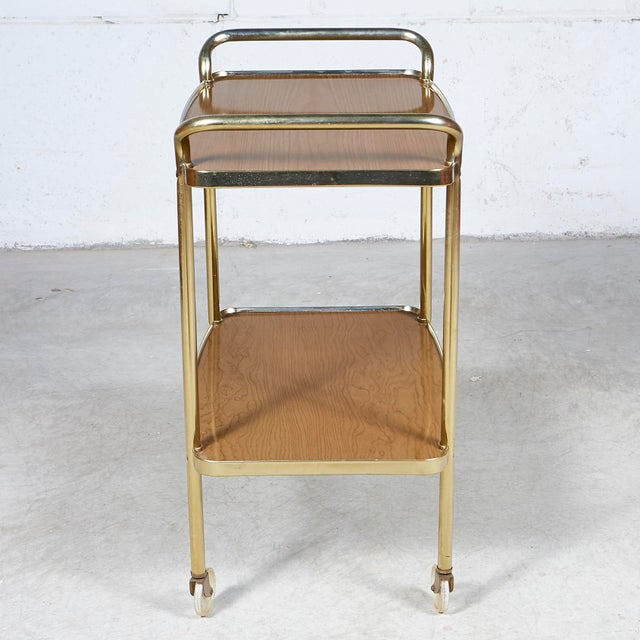 Vintage 1960s wood grain laminated two-shelf rolling serving cart by Cosco. The rolling cart has a gold metal accent....