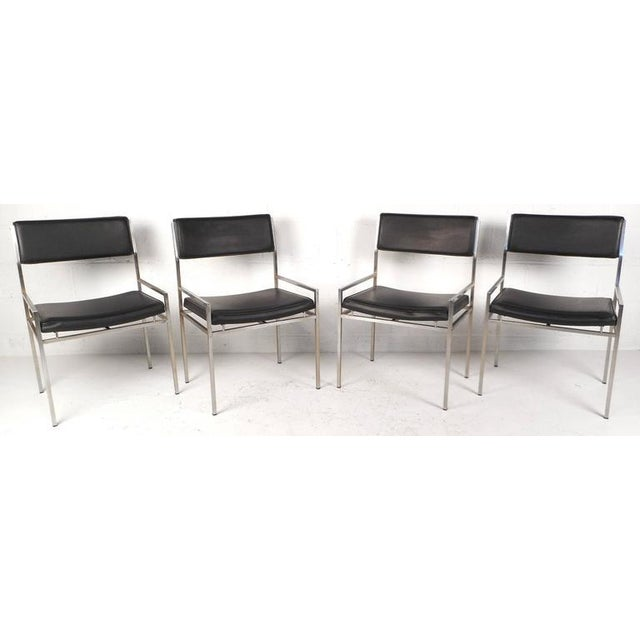 Stylish set of four vintage modern dining chairs feature unique low armrests, a sturdy chrome frame, and black vinyl...