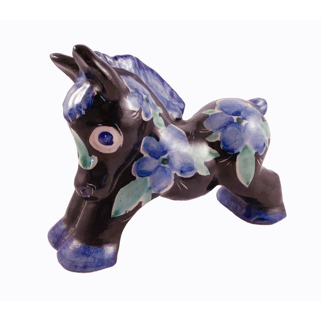 Beautiful studio art pottery donkey hand painted in a blue floral motif against a black background in excellent condition.