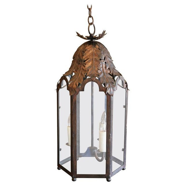 Two Italian style lanterns, six-sided tole and iron frames with glass panels and acanthus leaf decoration. Newly-wired for...