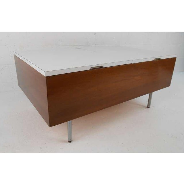 Mid-century coffee table with hinged white laminate doors, designed by George Nelson, ca. 1950s. Place of Origin:United...