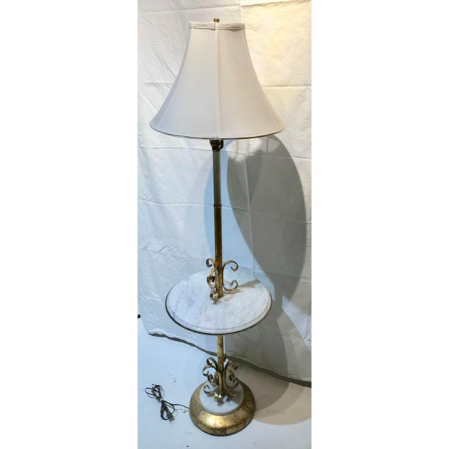 Beautiful gold leafed toleware marble floor lamp with wrought iron detailing. Base and table top have white Carerra...