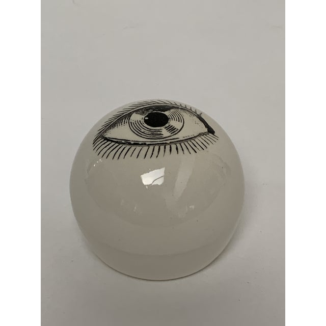 "Ceramic eye ball paperweight attributed to Piero Fornasetti, ca. 1960s. White ceramic weighted sphere measures about 3""..."