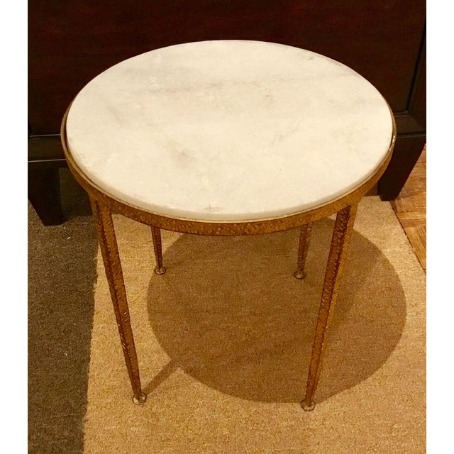 Arteriors modern round hammered side table in a gold leaf finished frame with a white marble top, showroom floor sample