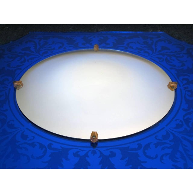 A stylish American art deco bull's-eye mirror with etched cobalt blue frame; centering a circular convex plate within a...