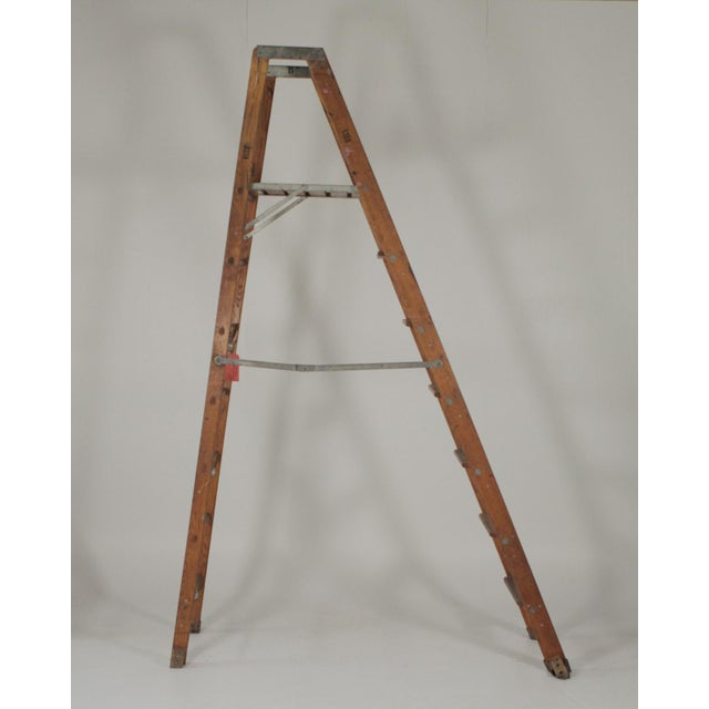 Early 20th century industrial folding ladder with a platform for safely standing. Great as a prop or display.