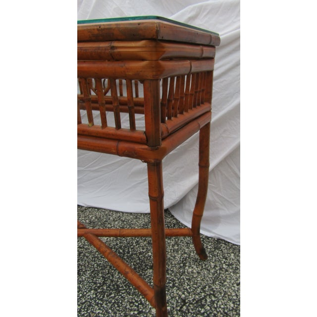 Vintage Bamboo Glass Topped Console Table. The bamboo table has a thick glass and the bamboo has an ornate designs. This...