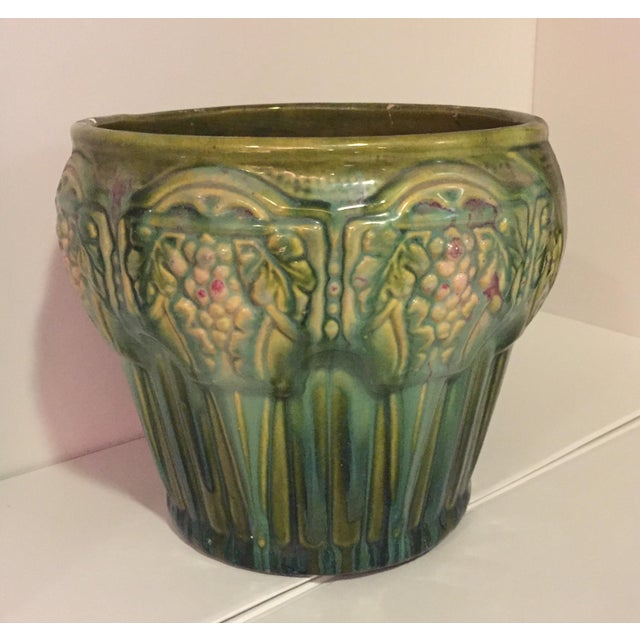 "Beautiful shades of green, with a few touches of burgundy on the grapes. Heavy glazed ceramic cachepot. Top diam . 8"" Base..."