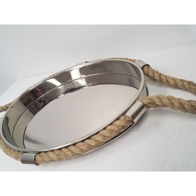 This is a very stylish nickel plated tray with a high ridge. The handles are rope and go around the complete tray. Around...