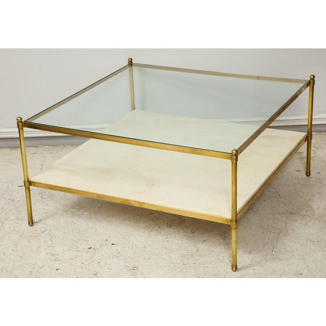 Parchment and bronze coffee table with glass top.