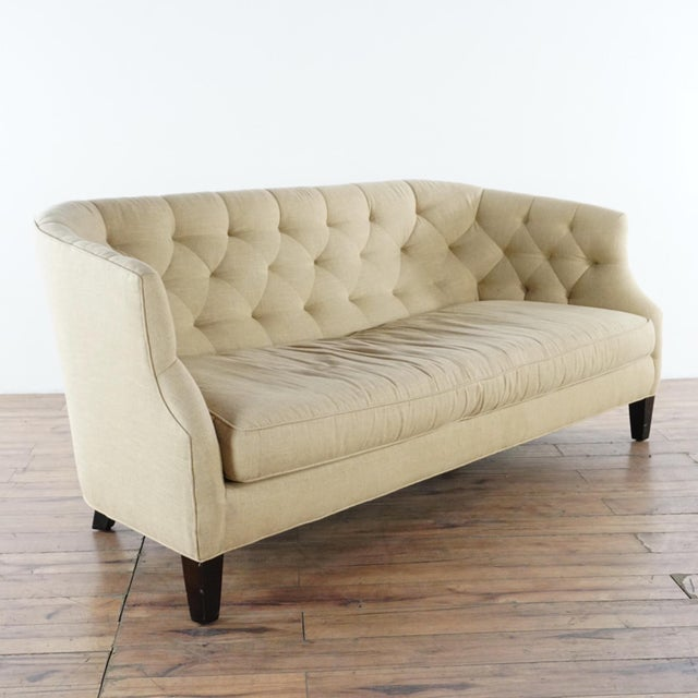 Single cushion. Raised on wood legs. Bearing the original label by the maker. Brand is Crate & Barrel. Dimensions (in):...