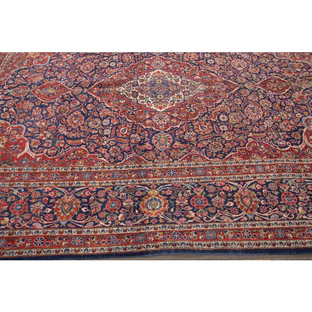 A hand-knotted Antique Persian Kashan Rug with a geometric design on a multi-color field. This rug is made of wool and...