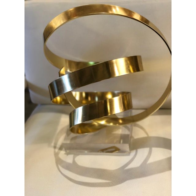 Gilt aluminum abstract sculpture signed and dated 1979 by Dan Murphy mounted on a custom Lucite base.