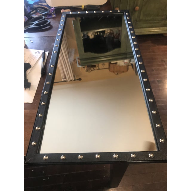 This studded leather-look mirror is mounted on brackets to go on a display rack. Brackets are pictured. It's a pretty cool...