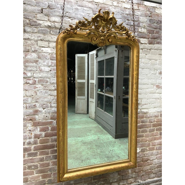 This 19th Century Mirror is adorned with floral and foliate patterns with a shell as main motif in the crest. Both mirror-...