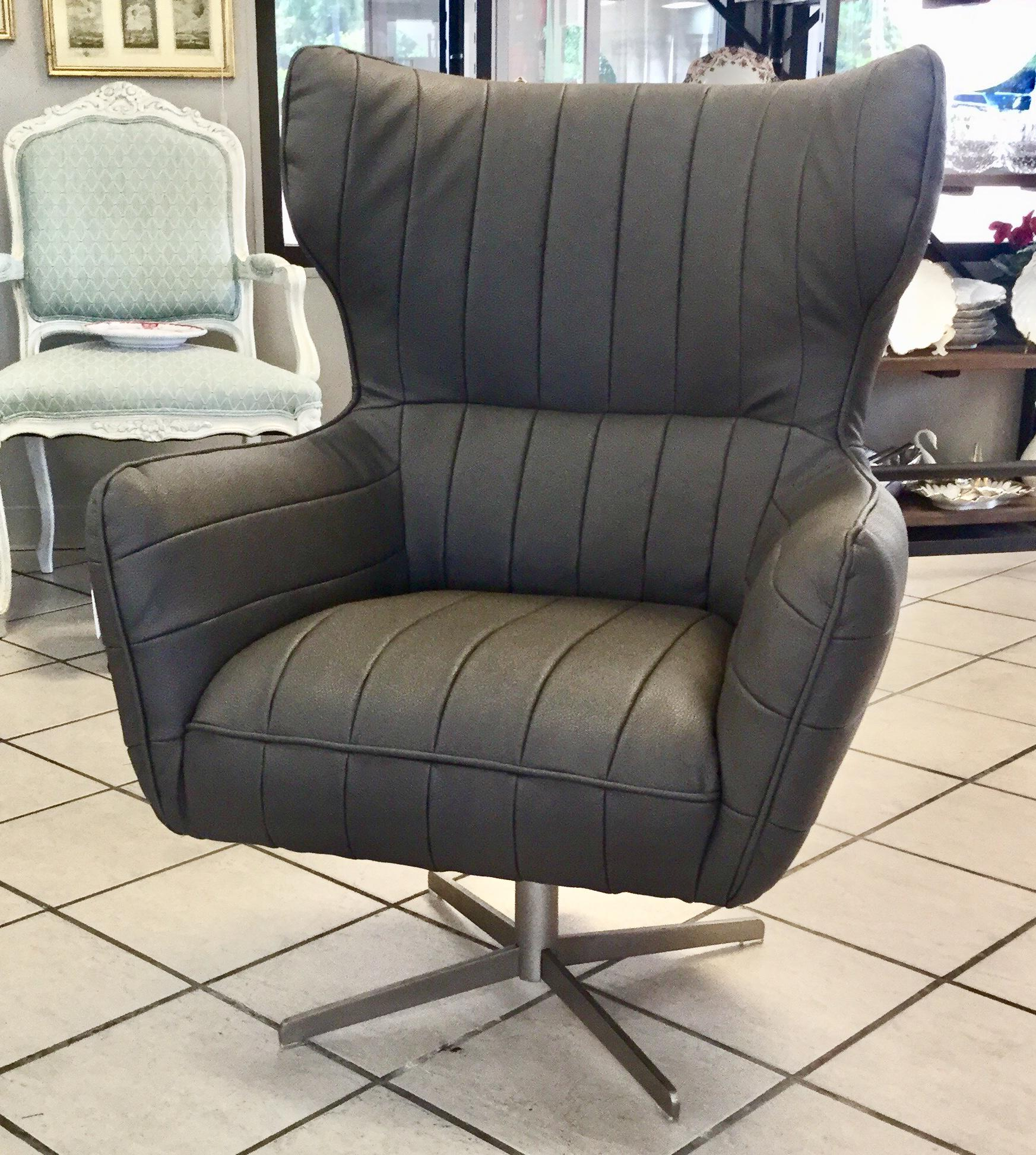 Large, Grey Leatherette Armchair Supported By A Metal Pedestal With Four  Legs. The Slight