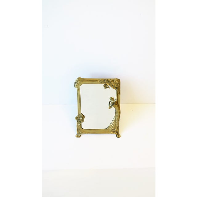 A brass vanity table mirror in the Art Nouveau style, circa late 20th century. A solid brass frame featuring women and...