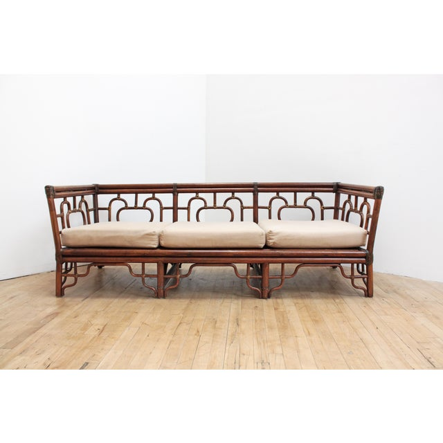 Rare vintage Chinese Chippendale rattan sofa with leather bindings. Six zippered cotton canvas cushions. Interior foam is...