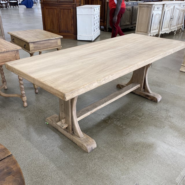 French bleached walnut trestle dining table with double pedestal and solid stretcher base. Coated in a flat finish.