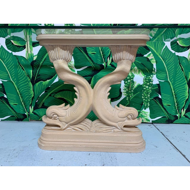 Sculptural Chinoiserie console table features a pedestal of twin Asian dolphins holding a beveled glass top. Cast plaster...
