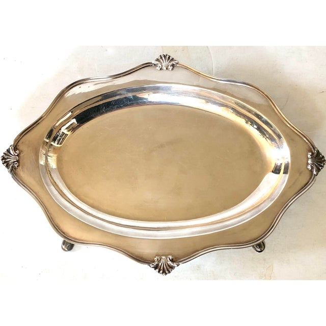Sheffield silverplate serving tray with pad feet. Shell motif along curved piped edges and deep well to hold sauces....