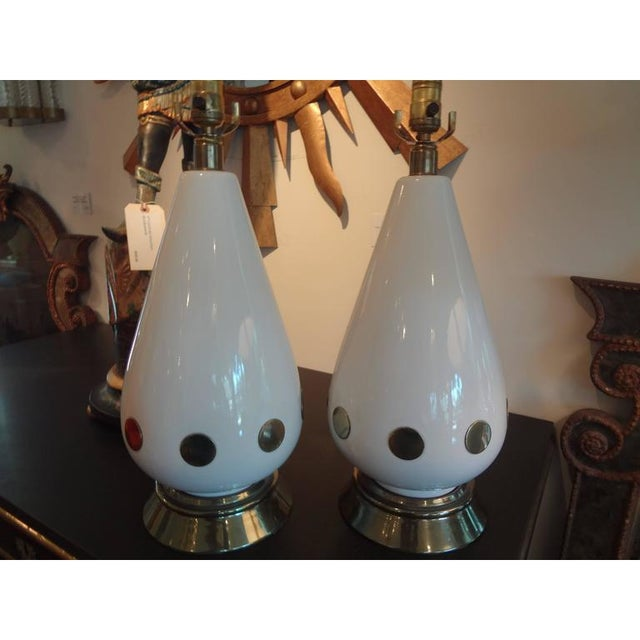 Glamorous pair of high style Italian porcelain lamps with applied brass disks, newly wired for U.S. market. This pair of...
