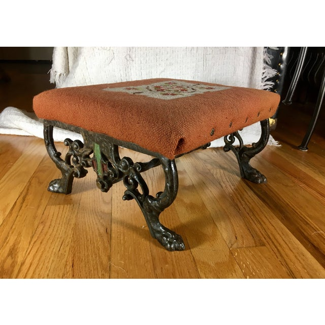 Beautiful, turn of the century Kingman footstool with floral needlepoint top and decorative cast iron claw foot legs. All...
