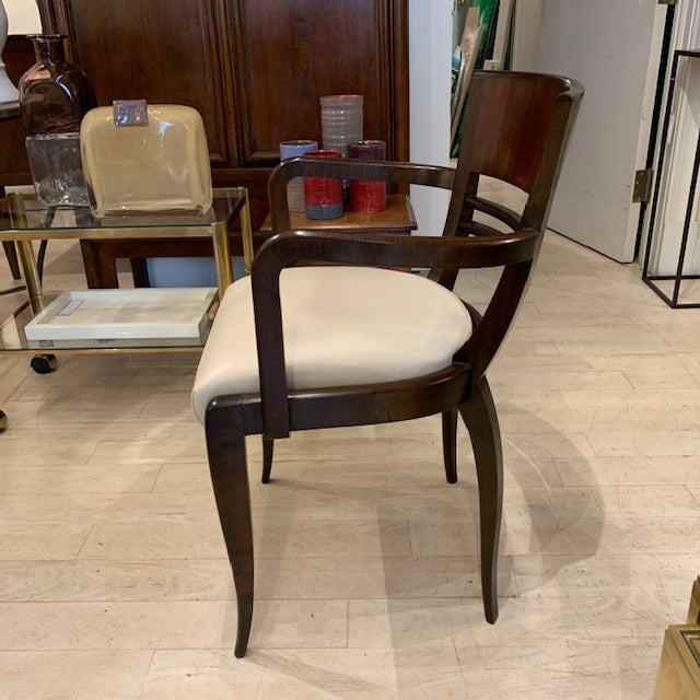 Pair of curved back rosewood arm chairs with tapered legs. Newly upholstered cream leather seats. France, circa 1950.