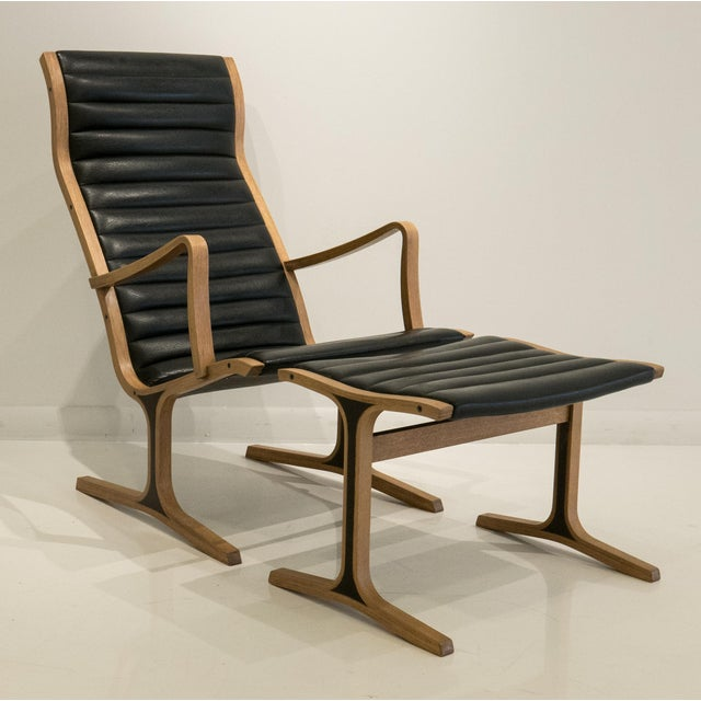"Sinuous ""Heron"" chair and footrest of two-tone laminated and steam-bent Japanese oak with channeled vinyl seat. Designed..."