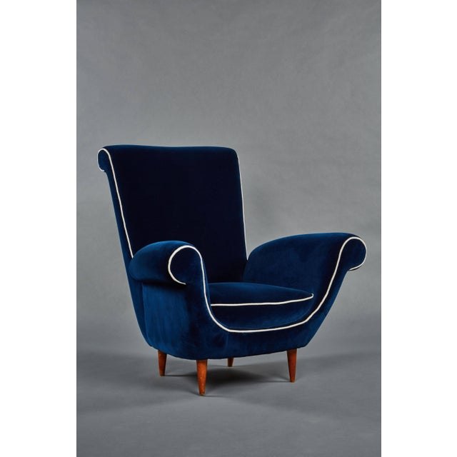 A pair of Ico Parisi attributed blue velvet armchairs. Scrolled details are sharply accentuated by a white linen welt....