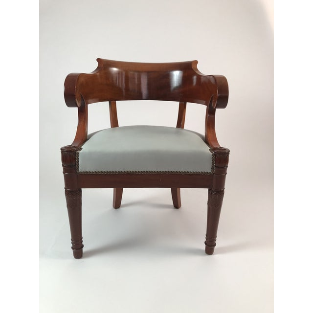 An early 19th century French Empire period fauteuil in mahogany, the curved backrest terminating in carved scrolled...