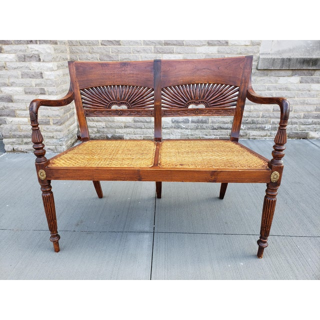 Antique Mahagony carved wood settee with a scroll back and caned seat. The settee has carved wood accents all around the...