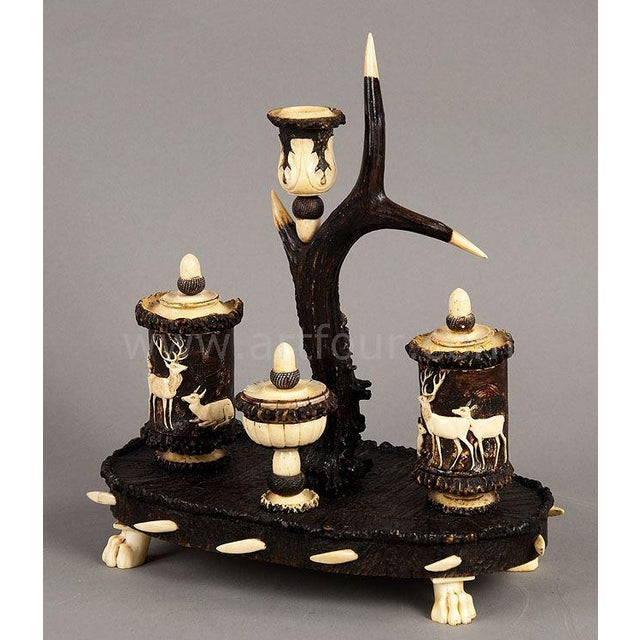 rare writing set made of original antlers with fine carved hunting scenes. base covered with antler pieces. executed ca....