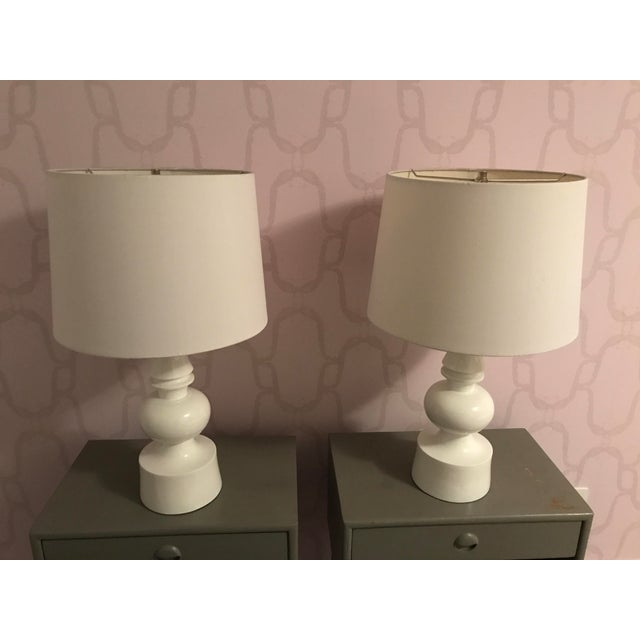 Pair of white turned table lamps with finials. Modern but classic white lacquered table lamps with large drum shades.