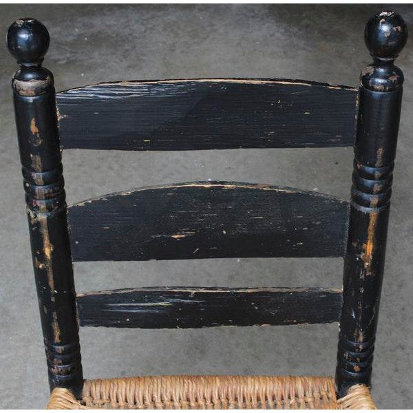 An antique hand hewn chair with rush seat. The chair is wood with a black finish and features a ladderback style with...