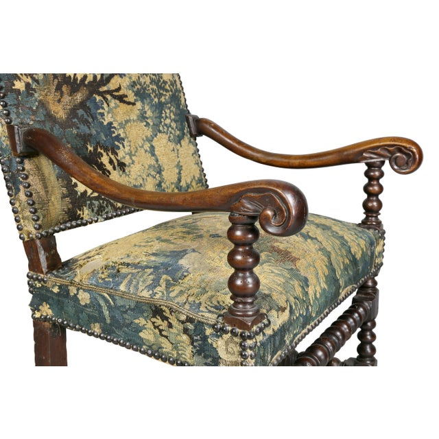 Antique armchair upholstered in Flemish tapestry, rectangular back and square seat, carved arms, turned legs and...