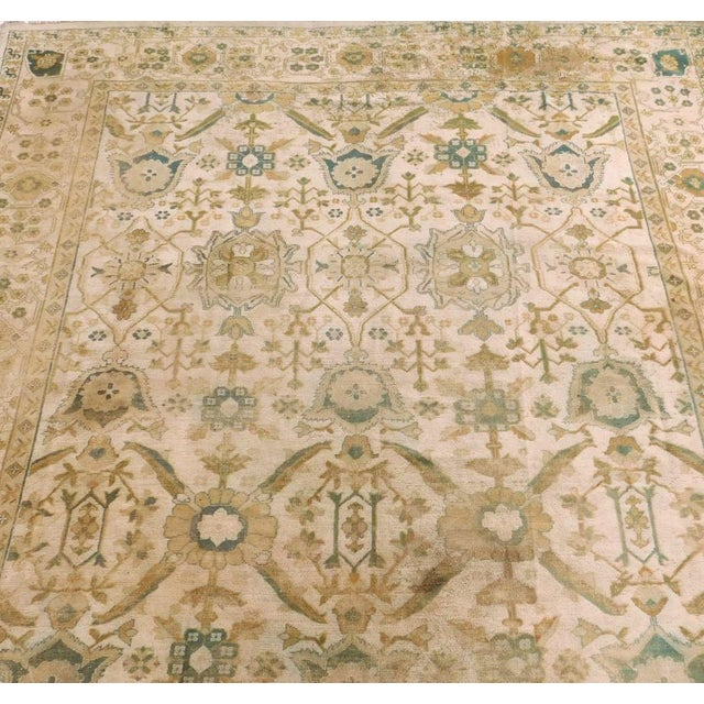 Scattered wear throughout the rug. Distressed worn condition. Antique Indian rug in Oushak desingn.