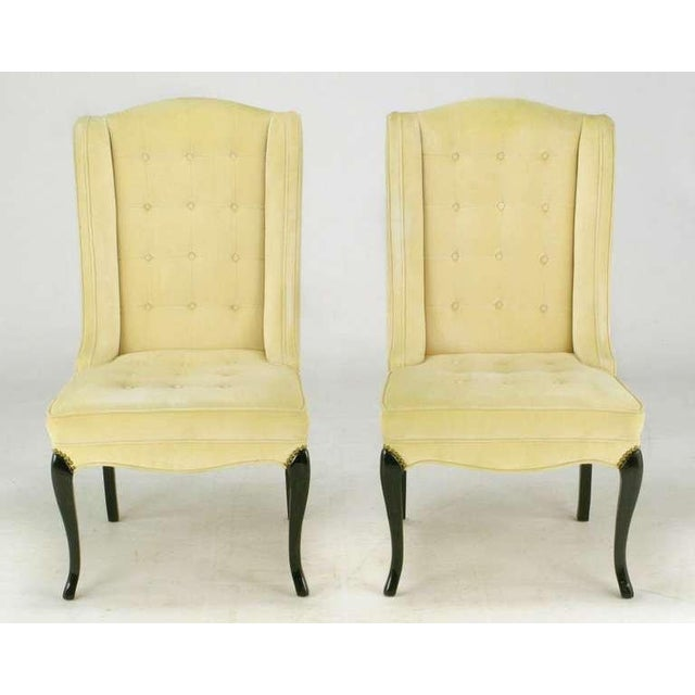 Elegant pair of creamy camel velvet clad slipper chairs, with button tufted seats and backs. Sinuous front and back carved...