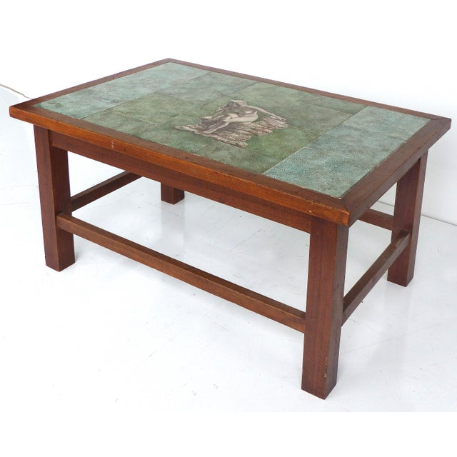 A Mid-century Modern tile top table hand painted by ceramist Johannes Meyer. The central tiles depict a nude female bather...
