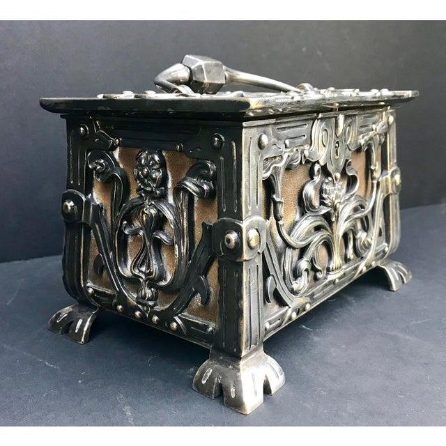This is an important and exquisite Art Nouveau footed silvered bronze jewelry box. The ornate bronze floral design covers...