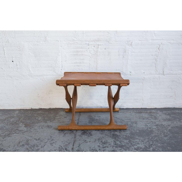 This small, rare folding stool is a piece to be adorned. With a beautiful leather seat and teak frame, it has a Native...