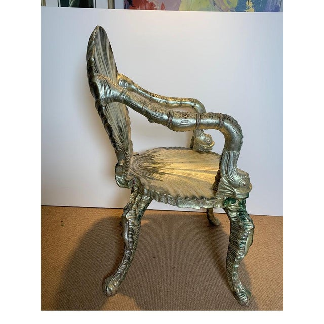 A pair of Venetian carved wood silver leaf grotto chairs. Whimsically carved chairs with shell back and seat, dolphin arms...