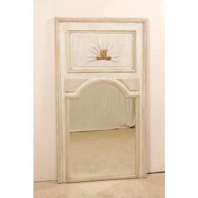 A tall French painted wood trumeau mirror from the 19th century. This antique mirror from France features the tall...