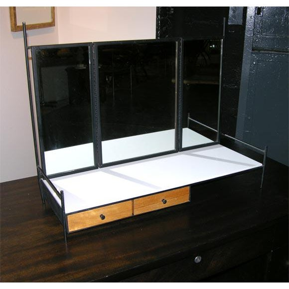 A Mid Century Modern wing folding dresser top vanity mirror in black enameled steel with two Birch drawers and white...