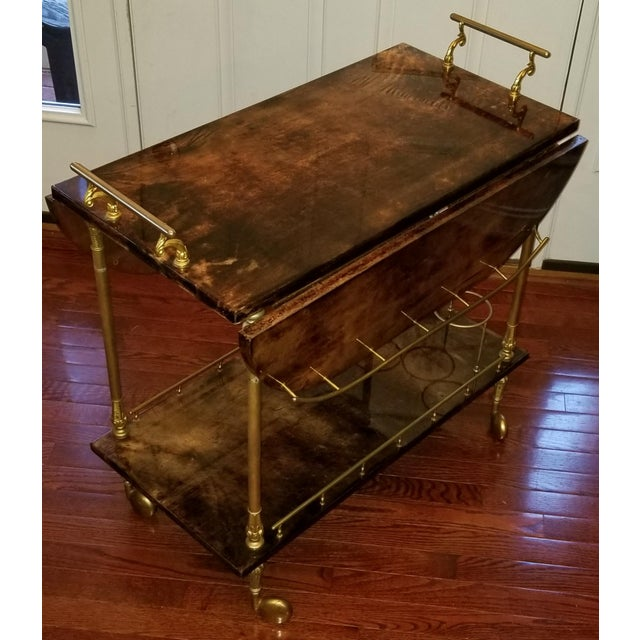 Vintage bar cart by Aldo Tura features lacquered goat skin parchment and brass hardware. Made in the 1960s.