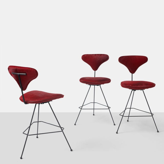 Arthur Umanoff Bar Stools A group of three bar stools with a swivel seat and black iron frame. The seat and back have been...