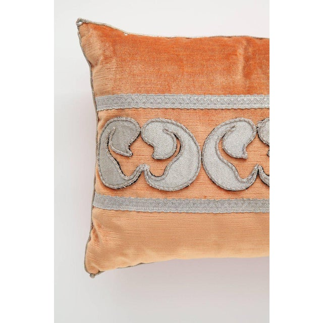 A stunning pillow in a tangerine velvet accented with antique metallic fragments forming a design between a border of...